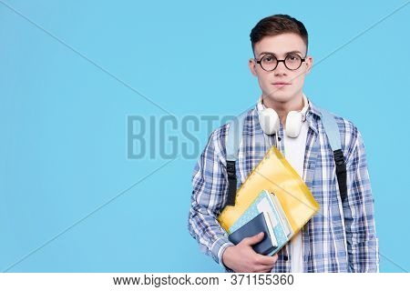 Young Man In White T-shirt, Checkered Shirt, Glasses, Headphones Is Holding Books, Notebooks, Standi