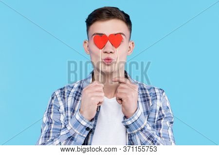 Young Man In White T-shirt, Checkered Shirt Is Holding In Hand Paper Decorative Red Heart Icons, Sig