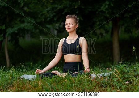 Frontal Portrait Of A Young Woman In Black Sportwear Seated On A Yoga Mat In Position Lotus In The P