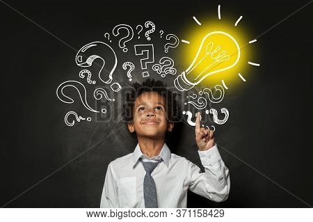 Clever Little Boy On Black Background With Light Bulb. Brainstorming And Idea Concept
