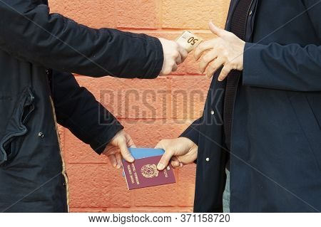 Two Men Exchange Italian Passport And Money - Concept Of Illegal Immigration, Sale Of Fake Passports