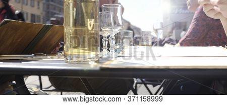 Perspective View Of Tables In Outdoor Restaurant. People Waiting For Order. They Reading Menu, The P