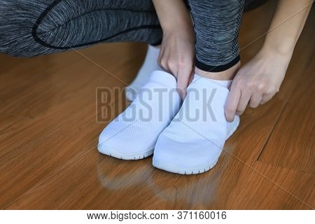 Girl Puts On Snow-white Sport Shoes, Getting Ready For Sports Training At Home. Close Up, No Face. F