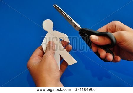 'Training or nurturing employee' - an idea. Paper-people cutout is being cut by a scissor, close up of a male hand.