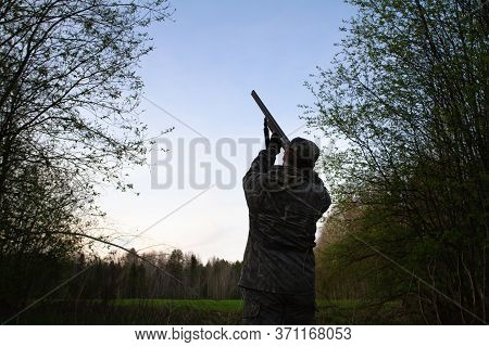 A Hunter With A Shotgun In His Hands Stands At Dusk In A Forest Clearing And Aims At The Night Sky