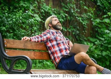 Doing Research. Successful Entrepreneur. Mature Man Sitting On Park Bench With Laptop And Checking E