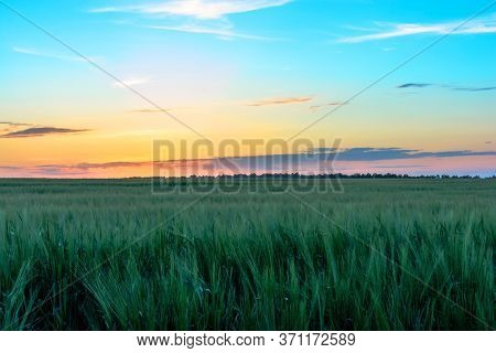 Sunset Sunrise Over Field Or Meadow. Bright Dramatic Sky And Dark Ground. Countryside Landscape Unde