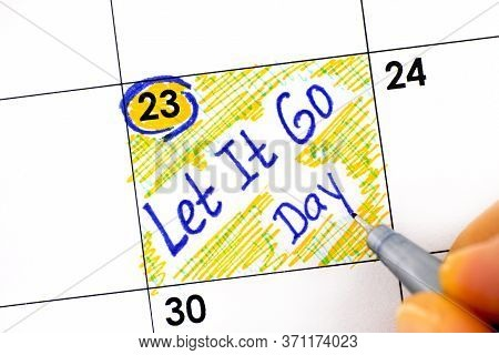 Woman Fingers With Pen Writing Reminder Let It Go Day In Calendar. June 23.