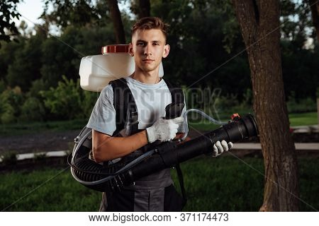 Man Spraying Insect Repellent. Gardener With Insect Sprayer.