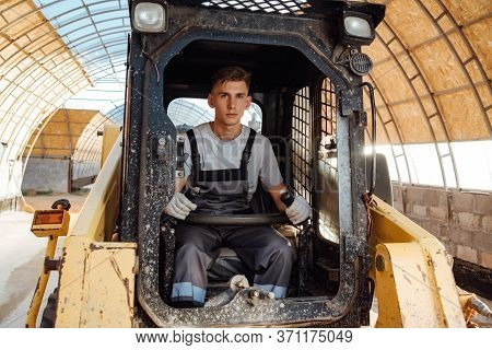 A Man In Overalls Driving A Tractor. Worker Sitting On His Tractor