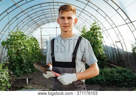Man With Garden Tools.young Happy Farmer Posing With Abrasive Tools In A Greenhouse