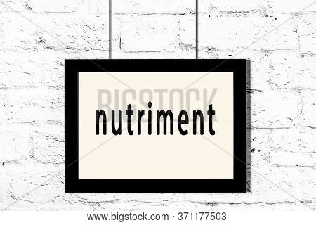 Black Wooden Frame With Inscription Nutriment Hanging On White Brick Wall