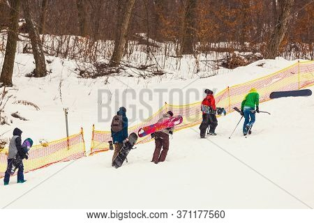 Joyful Snowboarders, With Snowboards In Their Hands, Go Up The Mountain Slope, Amidst Huge Snow-cove