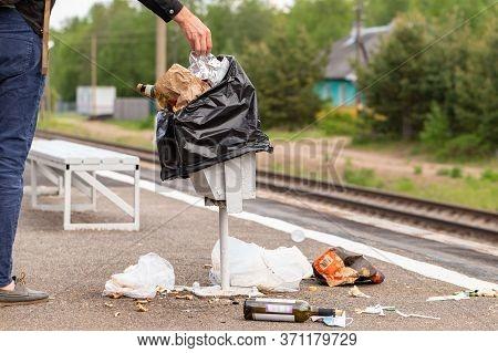 Hand Of Unknown Man Throws Trash Into Overcrowded Trash Basket On A Railway Platform. Garbage Bin. A