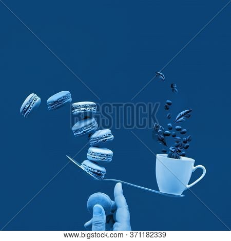 Monochrome Blue Color Toned Image. Balancing Cup Of Coffee And Macaroons On Index Finger. Perfect Ba
