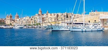 Panoramic Image Of Birgu Marina With Modern And Traditional Architecture Under Blue Sky. Sailing Boa