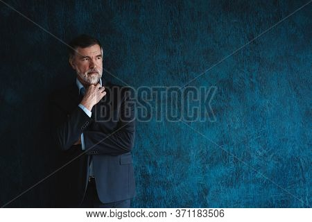 Serious Mature Man Posing In Front Of A Dark Blue Background With Copy Space.