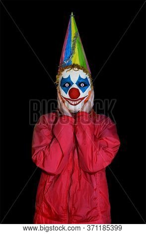 Surprised Masked Man In A Clown Mask On An Isolated Black Background. Scary Halloween Costume