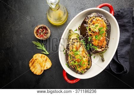 Baked Aubergine Or Eggplant Boats Stuffed With Mushrooms, Vegetables And Cheese On Black Background,