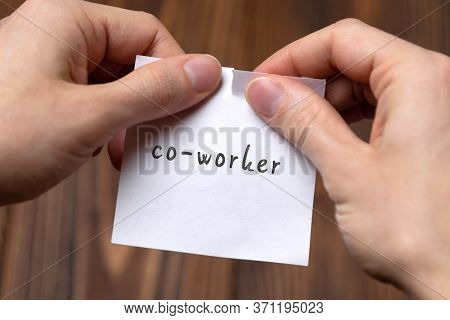 Concept Of Cancelling. Hands Closeup Tearing A Sheet Of Paper With Inscription Co-worker