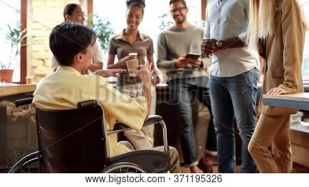Portrait Of Young Male Office Worker In A Wheelchair Drinking Coffee And Chatting With Colleagues Du