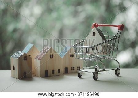 Shopping Trolley Basket With Wooden House In Pushcart. Choose Housing Loan That Right.