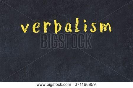 Chalk Handwritten Inscription Verbalism On Black Desk