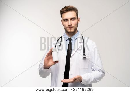 Smiling Doctor Holding A Bottle Of Tablets Or Pills With A Blank White Label For Treatment Of An Ill