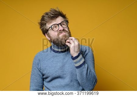 Shaggy Pensive Man In Glasses And An Old Sweater Is Trying To Remember Something By Touching His Bea