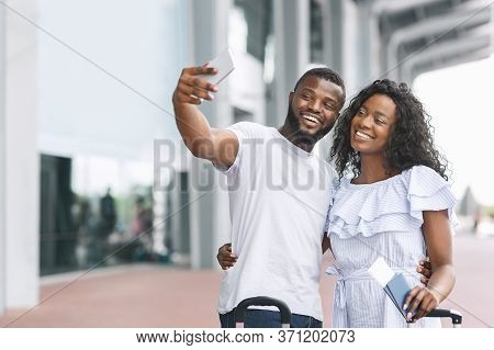 Honeymoon Memories. Happy Romantic Black Couple Taking Selfie Near Airport Terminal, Ready For Trave