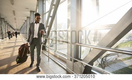 Business Travel Concept. African Businessman Texting On Cellphone Walking With Suitcase In Airport I
