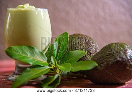 Avocado Cream (persea Americana Mill) In Bowl Between Leaves And Fruits And Aged Red Wood Background