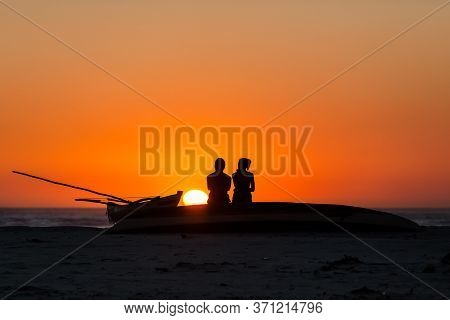 Silhouette Couple At Ocean Beach. Golden Light