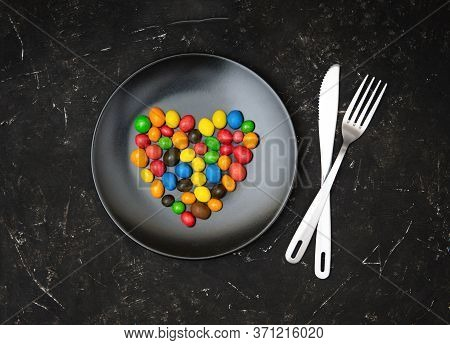 Multicolored Candy Dragees Arranged In Shape Of A Heart On A Matte Black Plate, Knife And Fork On A