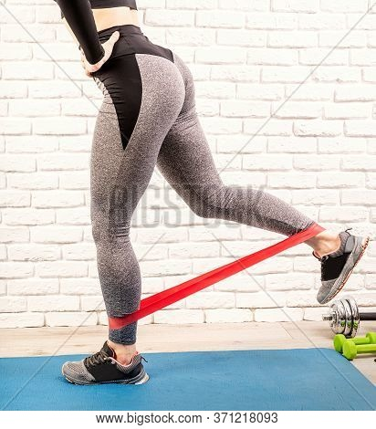Woman Exercising Legs At Home Using Rubber Resistance Band