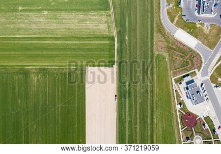 Top-down View Of Plowed And Planted Fields. A Tractor Plows A Piece Of Land. Taken Perpendicular Dow