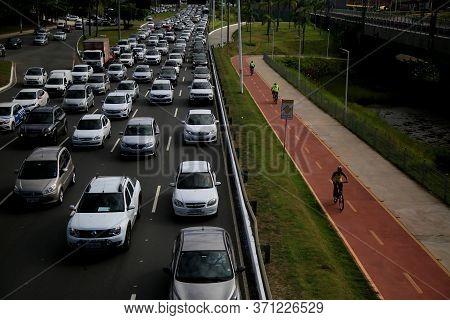 Salvador, Bahia / Brazil - Novembro 19, 2019: Cyclist Rides A Bicycle Lane Next To Congested Vehicle