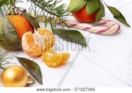 Fresh Tangerine, Whole Tangerines, Spruce Branches, Lollipop, Golden Christmas Ball On A White Backg
