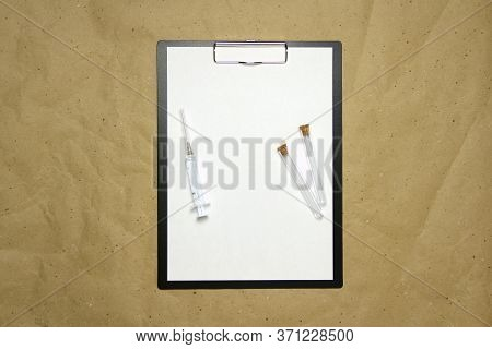 The Tablet With A Clip For The Clip Of Paper With A White Sheet A4 Lies Against The Background Of Cr