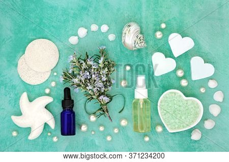 Skin care beauty treatment with fresh rosemary herb & cosmetic beauty products. Has astringent & anti ageing benefits and helps to reduce environmental skin damage. Flat lay on mottled turquoise.