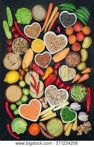 Vegan food for a healthy heart concept with foods high in protein, vitamins, lycopene, minerals, anthocyanins, antioxidants, smart carbs & dietary fibre. Ethical eating. Flat lay on dark wood.