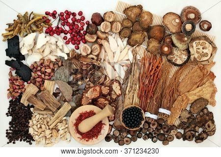 Large selection of traditional Chinese herbs & spices used in herbal medicine with tablets to boost chi levels on a bamboo mat & cream background. Alternative health care concept. Flat lay.