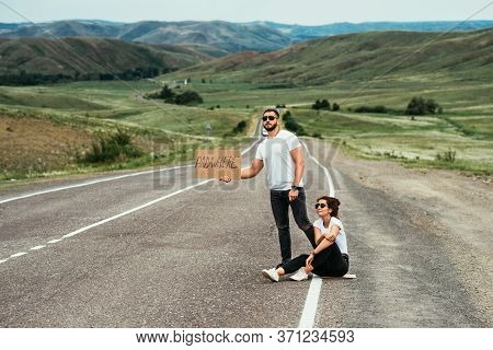 A Couple Hitchhiking. A Man And A Woman Catch A Car By The Road. A Young Couple Votes On The Road. A