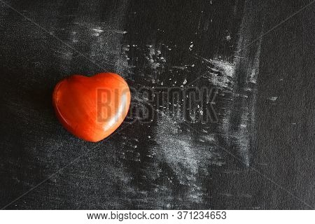 A Close Up Image Of Red Jasper Heart Shaped Crystal On A Black And White Background.
