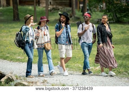 Group of young multi-ethnic friends walking path together and talking while enjoying weekends at festival campsite