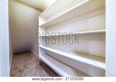 Small Walk In Closet With Empty Long Cabinet Shelves Under Slanted Ceiling