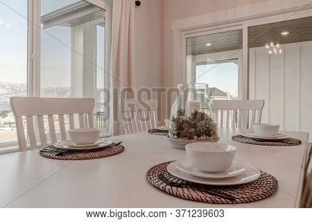 Dining Table With Tableware And Woven Placemat Arranged Around A Centerpiece