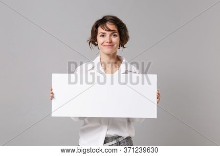 Smiling Pretty Young Business Woman In White Shirt Posing Isolated On Grey Background. Achievement C