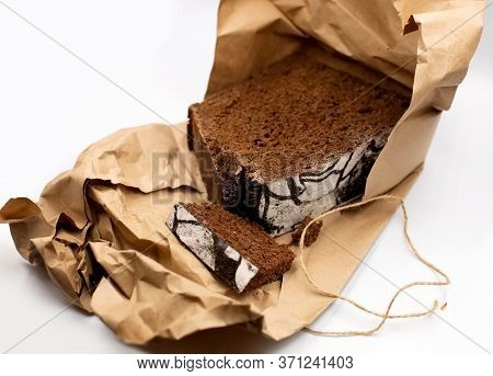Home Cooked Healthy Wholegrain Rye Dark Traditional Russian Bread Loaf In Rustic Craft Paper On Whit