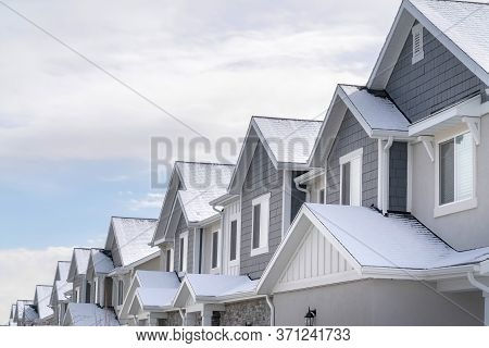 Facade Of Snowy Townhouses In South Jordan Utah Against Cloudy Sky In Winter
